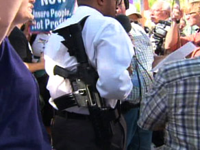 A pro-tie fashionista is shown legally carrying a rifle at a protest against President Obama in Phoenix, Arizona. (Photo via CNN and Getty Images).